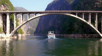 Three Gorges River cruise boat going under bridge