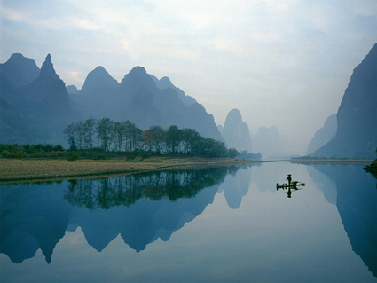 boat on Yangshuo river with mist and reflection of hills